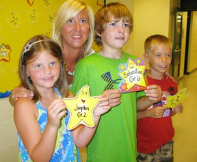 Jayden Smith (left), a Grade 2 student at St. Frances Catholic school, Sebastian Barham, a Grade 6 student, and Griffyn Kochany, a Grade 2 student, hold their Mathletics Gold Stars they achieved for completing a math computer program. With them is Grade 2 teacher Leanne Howse. School ends for the summer this week. (DANIEL R. PEARCE Delhi News-Record)
