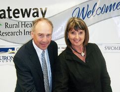 Gateway Rural Health Research Institute president Gwen Devereaux cuts a celebratory cake with Dr. Dave Edwards, of the University of Waterloo's School of Pharmacy as the two organizations renew their Memorandum of Understanding.