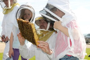 Richard Krahn holds a frame from a bee hive to show his kids Abigail, 10, and Matthew, 8 during a demonstration at the 60th annual Beekeepers' Field Day at the Beaverlodge Research Farm, June 21. The Krahns, who live just west of Beaverlodge, have just started keeping bees with three hives this year. (Diana Rinne Peace Country Sun)