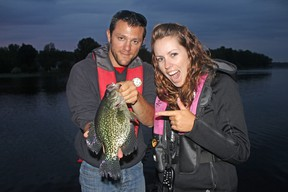 Jerome Richard, left, of France, holds a 13.5-inch black crappie caught and released in the Bay of Quinte while visiting columnist Ashley Rae, right. (Caroline Richard)
