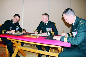 SEAN CHASE sean.chase@sunmedia.ca 2 Area Support Group commander Colonel Kerry Horlock (centre) watches as Maj. Jeff Spitzig (right) signs over command of 2ASG Operations Services to Lt.-Col. Chris Henderson during ceremonies at Garrison Petawawa Thursday. For more community photos please visit our website photo gallery at www.thedailyobserver.ca.