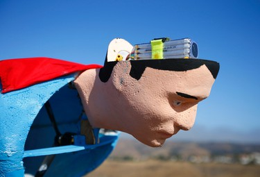 A radio-controlled Superman plane has a new battery placed inside his head as designer Otto Dieffenbach prepares for a test flight in San Diego, June 27, 2013.   REUTERS/Mike Blake
