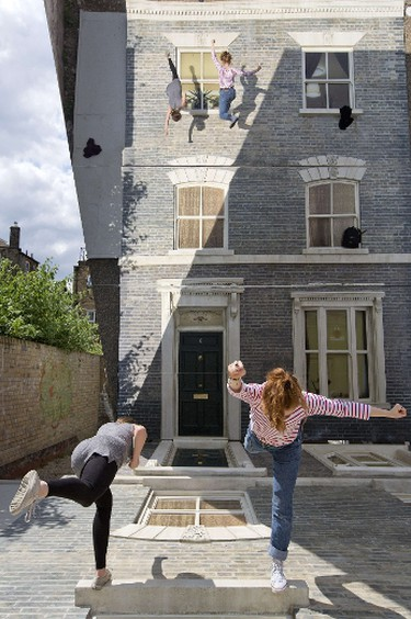 """People interact with a large-scale installation art piece by Argentinian artist Leandro Erlich, entitled """"Dalston House"""", in East London. AFP PHOTO/JUSTIN TALLIS"""