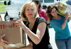 Laureen Harper, wife of Prime Minister Stephen Harper, helps unload the cavalcade of 15 vehicles loaded with supplies for the Morley emergency centre, June 26.