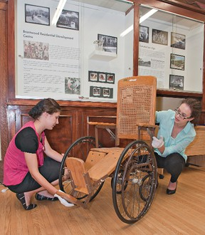 Curatorial assistant Kendra Gerber (left) and curator Chelsea Carss install an early 20th century wheelchair made of wood and wicker, part of a new exhibit at the Brant Museum and Archives in downtown Brantford, Ontario.  The exhibit chronicles the 100-year history of the Brantwood Residential Development Centre, which opened its doors as the Brant Sanatorium in 1913, a residence for tuberculosis patients. (BRIAN THOMPSON Brantford Expositor)