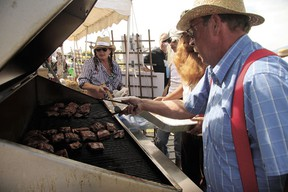 One of 2012's Leduc #1 rib cook-off entrants works on their racks.