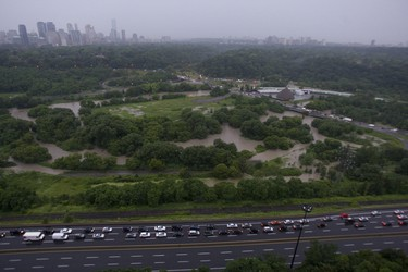 An aerial view of the Don Valley Parkway looking towards Bayview Ave. shows vehicles heading back north in the southbound lanes of the DVP and a GO Train stranded in the distance. A torrential downpour of 106mm over three hours shutdown Toronto on Monday July 8/13 submerging sections of roadways and highwaysand stranding motorists on the Don Valley Parkway. It was the second time in over a month ago that rains have shut down the main artery into the city.   Jack Boland/ Toronto Sun / QMI Agency