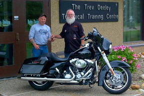 Following an exhausting nine hour drive, Vulcan, Alberta native Les Groves (left) receives the keys from Wally Beasler to his brand new 2013 Harley-Davidson Street Glide FLHX motorcycle courtesy of the Trev Deeley Technical Training Centre and the Harley-Davidson Motorcycle Raffle. (Daniele Alcinii/Fairview Post)