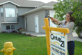 Jocelyn turner/Daily Herald-Tribune Century 21 real estate agent Brandi Martin hammers down a for sale sign on one of the available properties on 72 Avenue Wednesday morning. The property, Martin said, is just one of the available properties that may fit into the budget of a first time home buyer.