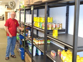 Joseph O'Neill, a volunteer with the Elliot Lake Emergency Food Bank, stands next to some of the organization's shelves that are low on some items. Photo by KEVIN McSHEFFREY/THE STANDARD/QMI AGENCY
