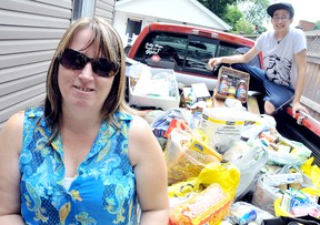 Ann Skelton and her son, Kyle, are amazed by the amount of non-perishable goods people donated for her second annual Memorial Food Drive after she put out a plea over Facebook. Skelton decided to make the summer donation to Outreach for Hunger in memory of her father, Russell McGee, who died 10 years ago, and brother Larry McGee who died a year ago Wednesday. Diana Martin/Chatham Daily News/QMI Agency
