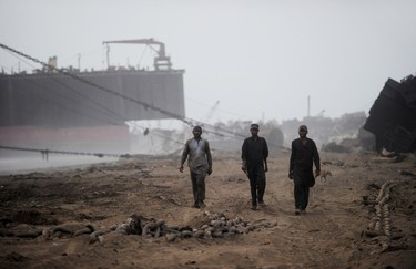 In this photograph taken on July 9, 2012, shipyard workers walk away from ships being dismantled and towards the shacks they call home at the end of their shift in one of the 127 ship-breaking plots in Geddani, 40 km west of Karachi. AFP PHOTO / Roberto SCHMIDT