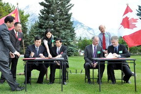 Director of the Mt. Huangshan Scenic Area Administrative Committee Jiwei Xu and minister of the State Forestry Administration Zhao Shucong sign the twinning agreement across from vice president of Western Canada Jeff Anderson and Banff National Park superintendent Dave McDonough on Sunday, July 14, 2013. Banff National Park now has a sister park — China's Huangshan National Forest Park. CORRIE DIMANNO/CRAG & CANYON/QMI AGENCY
