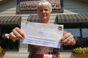 Port Stanley restaurateur Suzanne Van Bommel holds an anonymous letter which says her support for PrideFest this weekend in the community could cost her business. Eric Bunnell/QMI Agency/Times-Journal