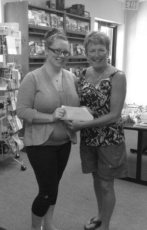 Pictured: Alisha Baker, a new staff member who is part of the special events team at the Chamber of Commerce presents Clarke with the cheque.
