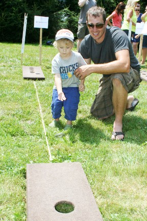 Three-year-old Cameron Hall of Blenheim, Ont., and his dad, Matt Hall, were among the 300 people who competed in the fifth annual Toss 'Em Up for Childhood Cancer ring toss tournament at the Holst farm near Woodstock on Saturday, July 20, 2013. The event held in memory of Nick VanDyk, Cassy Mann and Greg Schneider raises money in support of local participants in the Sears National Coast-to-Coast Ride for Children's Cancer. JOHN TAPLEY/INGERSOLL TIMES/QMI AGENCY