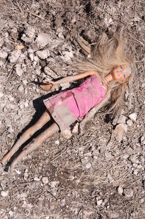 KEVIN RUSHWORTH HIGH RIVER TIMES/QMI Agency. Children's toys, such as this Barbie doll, covered in mud are a sign of lost memories and mementos never to be returned.