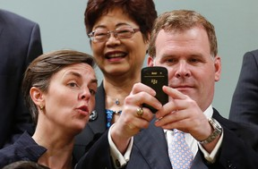 Canada's Foreign Minister John Baird (R) takes a picture of photographers and cameramen while posing with fellow cabinet ministers during a swearing-in ceremony at Rideau Hall in Ottawa July 15. Also pictured are Minister of Labour and Minister for Status of Women Kellie Leitch (L) and Minister of State for Seniors Alice Wong. CHRIS WATTIE/REUTERS