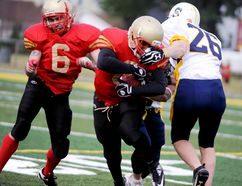 Sarnia Imperial running back Julian Shadd-Gentry, centre, gets facemasked on a run against the Sault Ste. Marie Steelers during a Northern Football Conference game on Saturday at Norm Perry Park in Sarnia. LIZ BERNIE/THE OBSERVER/QMI AGENCY