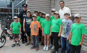 Timmins Police Const. David Ainsworth and Rob Knox, representing the owners of Tim Hortons restaurants in Timmins, presented a dozen youngsters with new bikes, helmets and other cycling accessories at the Timmins Police station Thursday. The presentation was made in recognition of the students achievements both in school and within the community.