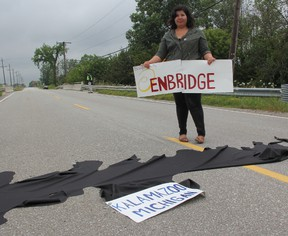 Vanessa Gray, of Aamjiwnaang and Sarnia Against Pipelines, recreated the Kalamazoo River oil spill during a LaSalle Line demonstration Saturday. ASAP members held the demonstration to draw attention to the spill caused by the rupture of a portion of Enbridge Line 6B. The group is lobbying against the reversal of Enbridge Line 9, which they fear could have similar consequences.