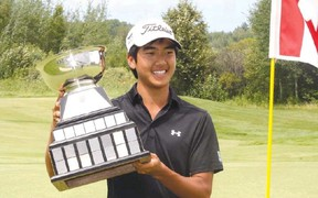 BEN LEESON The Sudbury Star Kevin Kwon, of Pitt Meadows, B.C., celebrates with the championship trophy after winning the Canadian Junior Boys Golf Championship at Timberwolf Golf Club on Friday.
