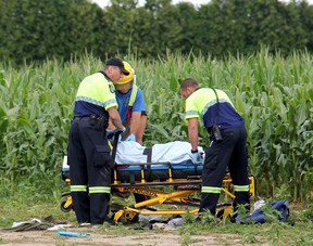 Emergency personnel attend to a teen boy who was injured after being hit by a vehicle near a cornfield on Jenner Line in the Harwich area on Monday near Chatham, Ont., around 12:30 p.m. ELLWOOD SHREVE/ THE CHATHAM DAILY NEWS/ QMI AGENCY