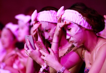 Participants arrange their facial masks after applying it to their faces in Taipei on July 28, 2013. A total of 1,213 people broke the Guinness world record by applying facial masks for 10 minutes at the same time, according to event organizers. (REUTERS/Pichi Chuang)