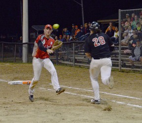 Wiarton Red Devils' first-baseman Ty Sebastian throws the ball home while Newfoundland's Johnny Doyle rumbles to first during a double life game on Friday at the 2013 Canadian Junior Men's Under-21 Fastball Championships.