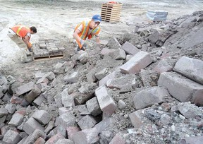At the municipal landfill site Monday, Aaron Erb-Ohnsorge, left, and Collin Dunn clean and stack some of the thousands of bricks recovered from the reconstruction of Shakespeare St. (SCOTT WISHART The Beacon Herald)
