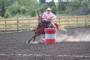 """Melvin Underwood WSAGC (Vice-president) rounding the barrels on his horse """"Red""""."""