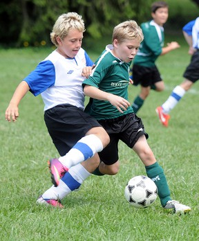 A Quinte West Bridge to Wealth U10 Wolverines player tries to fend off a Darlington Striker during semi-final action at the 17th annual Cameron Memorial Soccer Tournament, Sunday at Centennial Park.