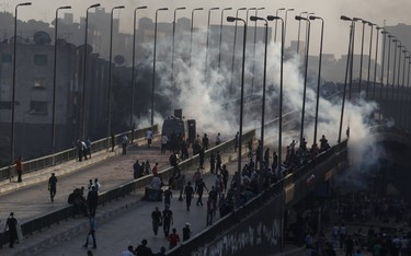 Members of the Muslim Brotherhood and supporters of ousted Egyptian President Mohamed Mursi flee from tear gas and rubber bullets fired by riot police during clashes, on a bridge leading to Rabba el Adwia Square where they are camping, in Cairo August 14, 2013. At least 95 Egyptians were killed on Wednesday after security forces moved in on protesters demanding the reinstatement of Mursi, and the government imposed a state of emergency as unrest swept the most populous Arab nation. REUTERS/Amr Abdallah Dalsh  (EGYPT - Tags: POLITICS CIVIL UNREST)