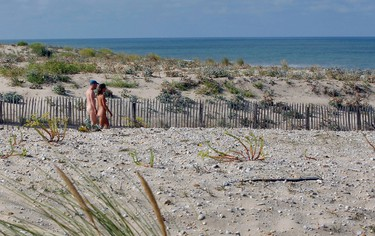 A couple walk between the sand dunes as they make their way to the beach at the Centre Helio-Marin (Center for Sun and Sea) naturist campsite on the Atlantic coast in Montalivet, southwestern France, August 2, 2013. The centre, created in July 1950, was the first vacation nudist camp to open in Europe. France is host to some 83 naturist sites where 60% of the holiday makers are foreigners. During the peak summer holiday period, 14,000 people spend their vacation at this nudist campsite on the Atlantic Ocean. REUTERS/Regis Duvignau