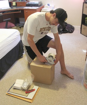 Sarnia Sting goaltender Brodie Barrick prepares a box to ship. Barrick spent his summer driving to garage sales and looking for bargains, before posting his purchases on eBay to make a profit. SHAUN BISSON/THE OBSERVER/QMI AGENCY