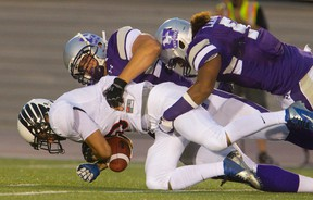 Westerns Mustangs Rupert Butcher and Beau Landry tackle Carleton?s Christian Battistelli during their Ontario university football game at TD Stadium Sept. 2. (MIKE HENSEN, The London Free Press)