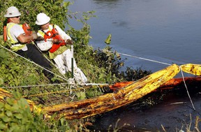 Cleanup workers tie absorbent booms to the shore of the Kalamazoo River in Battle Creek, Michigan after an oil  pipeline, owned by Enbridge, leaked an estimated 820,000 gallons of oil into the river near Marshall, July 31, 2010. REUTERS/Rebecca Cook