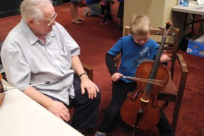 Volunteer Jim Coles keeps a watchful eye on Ryan MacIntosh, 5, as he tries his hand at playing the cello during the Kingston Symphony Association-organized Instrument Petting Zoo held Saturday in the lobby of the Grand Theatre as part of the city's Culture Days celebration. (PETER HENDRA The Whig-Standard)