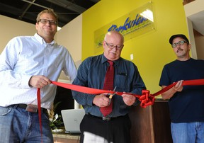Parkview Alliance Church's Lead Pastor Bryce Ashlin-Mayo holds the ribbon while Vermilion's mayor Bruce Marriott cuts the ribbon to celebrate opening of the new youth drop in centre.