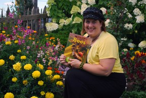Kari-Lynn Winters, a St. Thomas native and Brock University professor, holds a copy of her book Buzz About Bees in a garden at Clovermead Adventure Farm near Aylmer. Winters wrote the book to educate children about declining bee populations.