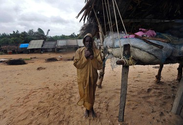 A man waits to be evacuated to a safer place as he stands near his fishing nets along the shore at the village of Donkuru in Srikakulam district, in the southern Indian state of Andhra Pradesh Oct. 12, 2013.