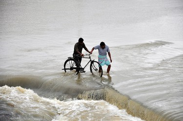 Men cross a flooded road after heavy rains caused by Cyclone Phailin at Gaghra village in the eastern Indian state of Jharkhand October 14, 2013. REUTERS/Stringer