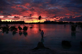 A villager wades through a small lagoon, which at high-tide laps at the base of homes, near the village of Tangintebu on South Tarawa in the central Pacific island nation of Kiribati May 25, 2013. (REUTERS/David Gray)
