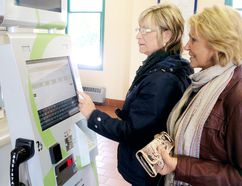 Cathy Boak of Wallaceburg, and Debbie Gobeil, far right, use the new automated ticket machine at the VIA station in Chatham to book tickets to London on Monday. BOB BOUGHNER/ THE CHATHAM DAILY NEWS/ QMI AGENC