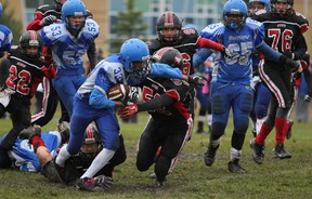 Griffin Brown and Nathan Dhanoa help Cumberland Panthers RB Fahan Younus run the ball against Myers Riders in Peewee action.