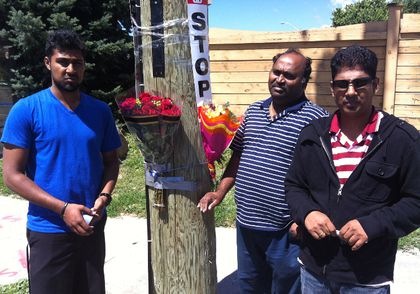 Relatives of Manoranjana Kanagasabapathy, Yathu Yogi, left, his dad Yogi Thambi, centre and Thambi's brother-in-law Vijay Nadarajah drop flowers on Aug. 14 at the Scarborough corner where the 52-year-old woman was killed as she boarded a TTC bus. (CHRIS D