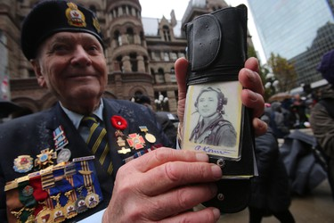 Armin Konn holds a photo of himself — he served with the Soviet Forces during the Battle for Berlin and now is with Royal Canadian Air Force cadets — during Remembrance Day ceremonies at the Old City Hall cenotaph on Monday, November 11, 2013. (Jack Boland/Toronto Sun)