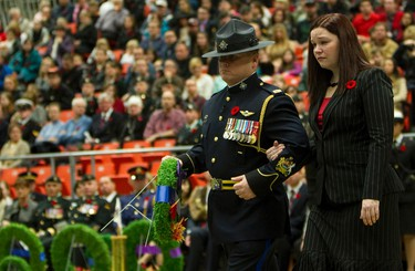 Silver Cross widow Amanda Anderson is escorted by Sheriff Sergeant Major Tim Turner, as she lays a wreath during the Remembrance Day ceremony in the Butterdome at the University of Alberta, in Edmonton Alta., on Nov. 11, 2013. David Bloom/Edmonton Sun/QMI Agency