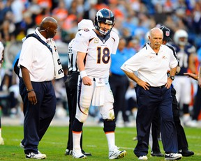 Broncos QB Peyton Manning (18) is looked at by members of the medical staff after being hit on a pass play during second half action against the Chargers in San Diego on Sunday, Nov. 10, 2013. (Christopher Hanewinckel/USA TODAY Sports)