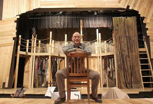 Tim Fort, director of the Queen's drama department play The Threepenny Opera, sits on the play's set. The audience is encouraged to tweet or send photos of the play during the performance.